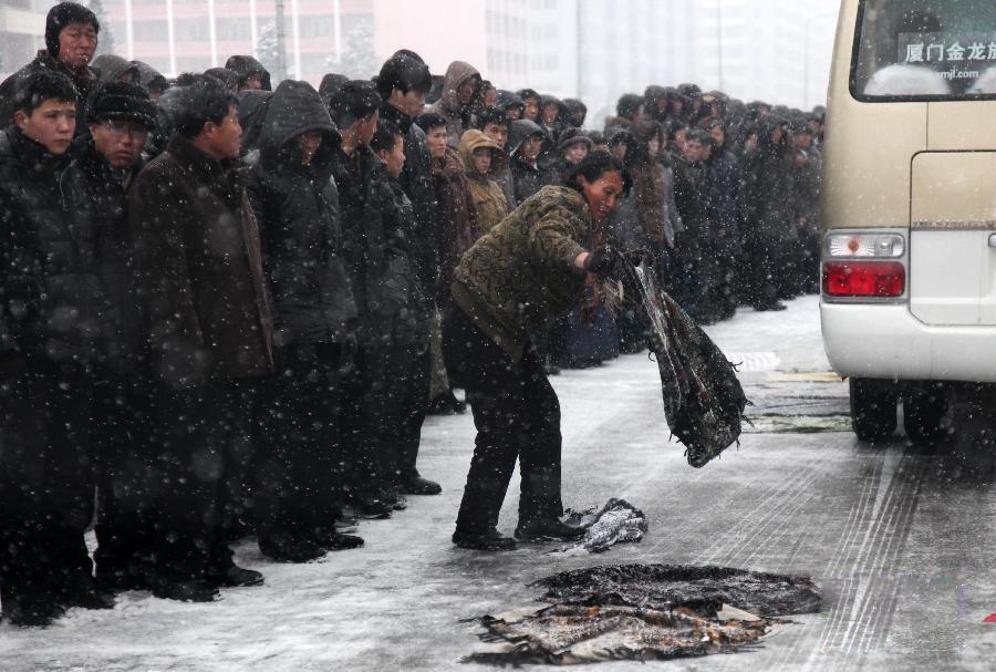 金正日葬礼 朝鲜民众衣物遮路防车辆打滑