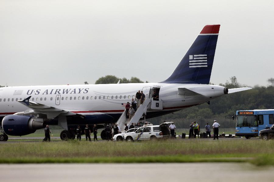 飞机降落后,执法人员将一名男子带下飞机