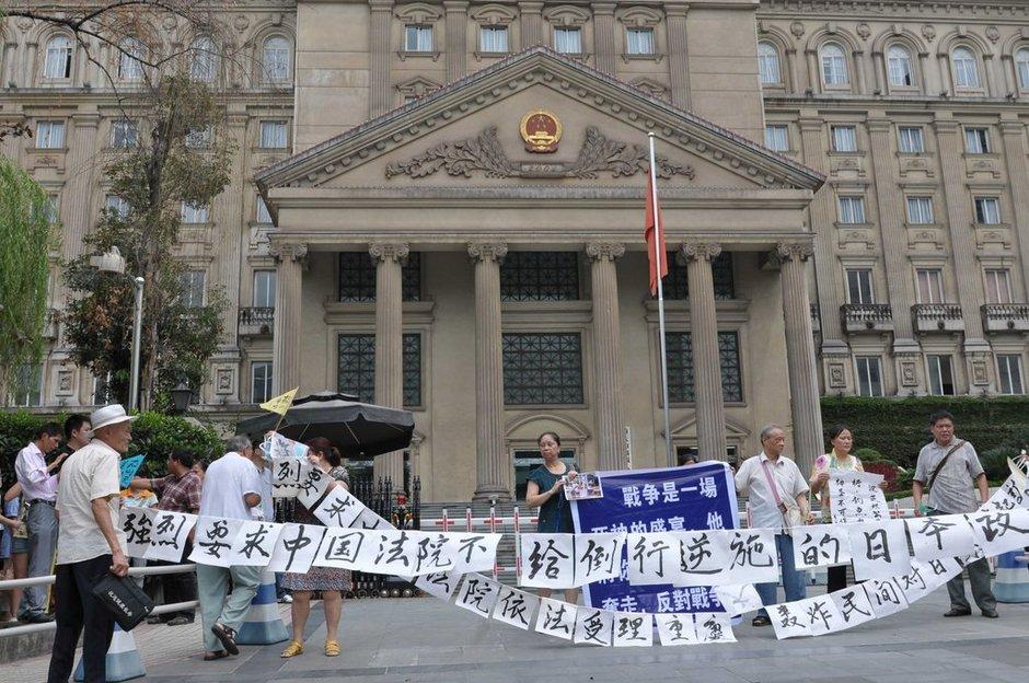 """北京时间2012年9月10日,重庆大轰炸受害者在重庆市高级人民法院办公大楼前声讨日本侵略罪行。   当地时间10日下午,15名""""重庆大轰炸""""受害者或其遗属向重庆市高级人民法院递交了民事起诉状,正式起诉日本政府,提出要求日本政府向受害者公开谢罪并进行赔偿等诉讼请求。   重庆高院将裁定是否立案   据""""重庆大轰炸""""受害者对日索赔律师团成员潘国平介绍,此次诉讼的被告是日本国政府,法定代理人为现任日本内阁总理大臣野田佳彦。每位原告的索赔金额不同,从150万元人民币到8000多万人民币不等。有的原告"""