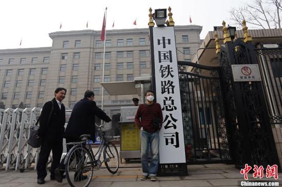 """3月17日上午,一名男子在新挂牌的中国铁路总公司牌前留影。当日早上,原""""铁道部""""牌匾被摘下,工作人员换上了""""中国铁路总公司""""的新牌。中新社发 张浩 摄"""