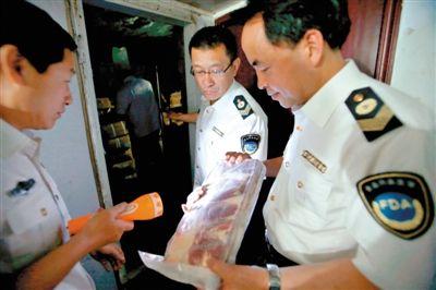 5月8日,山西运城市一名执法人员检查火锅店冷库的冻羊肉。新华社发