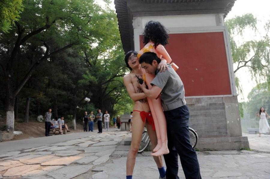 两男子北大裸奔遭质疑 抱充气娃娃为引起人们重视(组图)北京大学未名湖边有多名学生和游客在散步拍照。北京大学保卫部出动了十余名保安在湖边巡逻,一辆北京大学保卫部的金杯车停在博雅塔附近待命。有北大的学生称,如此多数量的保安较为少见。至昨天下午4点半,两名年轻男子全身只穿一条红色大象裤,每人手持一把吉他和一个充气娃娃从博雅塔西侧山上的树林中跑出来。