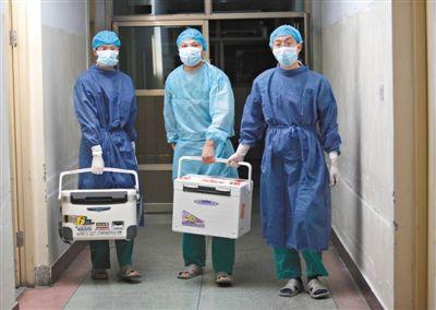 2012年8月16日凌晨,河南栾川县人民医院,医务人员提着装有捐献者胡小现器官的冷藏箱走出手术室。张晓理 摄