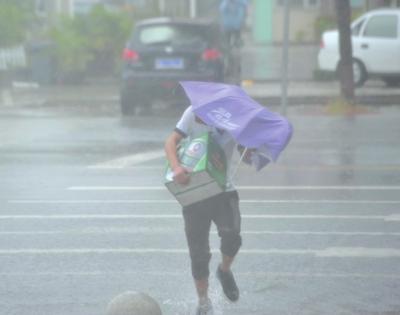 10日,三亚,一位行人冒雨过街。新华社发