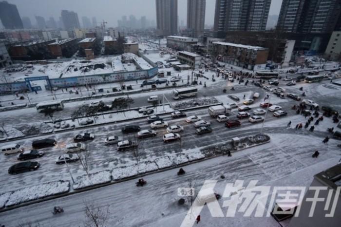 河南南阳,市民在下过雪的街道缓慢骑行,一旁的建筑工地显得格外萧条