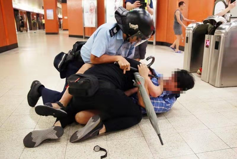 身穿蓝色格子衫的香港市民协助港警制服暴徒。来源:港媒